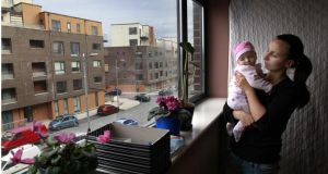 Priory Hall resident Katarzyna Bielecka pictured in 2011 with her daughter Liliana age 2 months looking out of her window. Photograph: Brenda Fitzsimons / The Irish Times