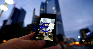 A passerby uses his smartphone to take a picture of the euro sign landmark in front of the headquarters of the European Central Bank  in Frankfurt yesterday.  Photograph: Kai Pfaffenbach/Reuters