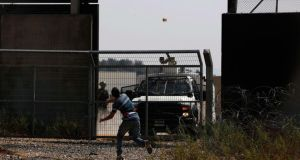 A Palestinian protester hurls a stone at Israeli troops during clashes after a protest, which was against Palestinian prisoners being held in Israeli jails, in the West Bank village of Bilin near Ramallah. Photograph: Mohamad Torokman/Reuters