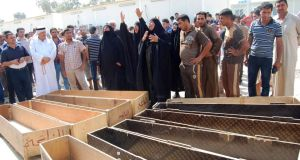 Women react near empty coffins as they wait to claim the bodies of their relatives, who were killed by gunmen, outside a hospital morgue in Mahmudiya, 30 km (19 miles) south of Baghdad, today.  Photograph: Ibrahim Jassam/Reuters