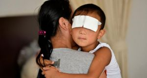 The six-year-old boy, whose eyes were gouged out, is held by his mother at a hospital in Taiyuan, Shanxi province  today. Photograph: Reuters