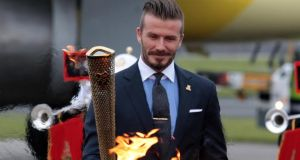David Beckham holds the Olympic flame in London – we find out today which city will host in 2020. Photograph: Getty.