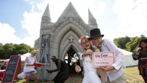Bestival goers Charlotte Rice and Calum Lyon, both 20, from the Isle of Wight, with their 'marriage' certificate after their 'wedding' in the Big Love inflatable church at Bestival. Photograph: Yui Mok/PA Wire