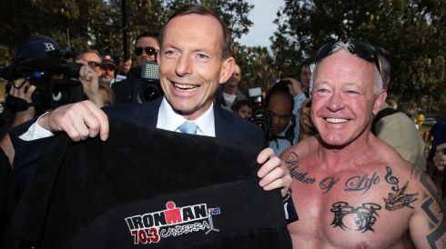 Tony Abbott poses with an Ironman Triathlon towel he received from a voter outside the polling station at the Freshwater Surf Life Saving Club in Sydney. Photograph: Brendon Thorne/Bloomberg