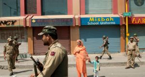 Indian security forces stand guard and shops are shuttered after a call for a strike to protest a performance by conductor Zubin Mehta in Indian-administered Srinagar, Kashmir, yesterday. Mehta's performance was met with widespread criticism, as many Kashmiris complained that the public would not be admitted to the event. Photograph: Manpreet Romana/New York Times