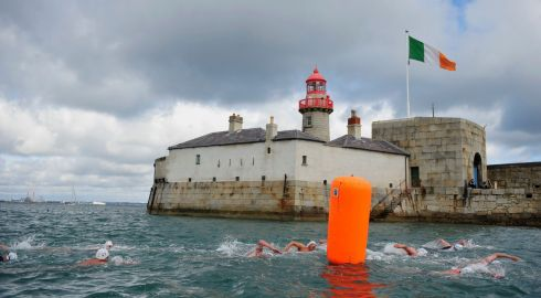 Patricipants in the Dun Laoighre Harbour swim pass by the East Pier Lighthouse during the annual race. Photo: Aidan Crawley