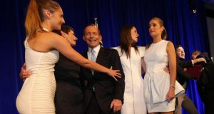 An unidentified man  is bustled  off the stage by security staff after Australia's conservative leader Tony Abbott poses for pictures with his family after his victory speech   in Sydney. Photograph: Reuters/Rob Griffith