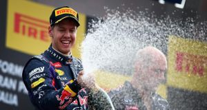Red Bull driver Sebastian Vettel celebrates on the podium after winning the Italian Formula One Grand Prix at Autodromo di Monza on Sunday. Photograph: Getty Images