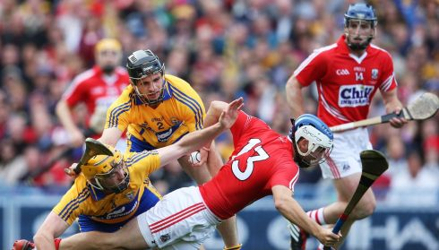 Clare's Cian Dillon and Domhnall O'Donovan tackle Luke O'Farrell of Cork. Photograph:  Cathal Noonan/INPHO