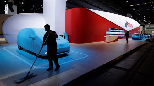 An employee sweeps the floor of the Toyota Motor Corp. automobile stand. Photograph: Jason Alden/Bloomberg