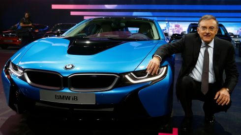 BMW CEO Norbert Reithofer poses beside the BMW i8 hybrid supercar.  Photograph: Ralph Orlowski/Reuters