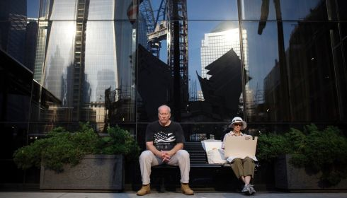 People sit before a moment of silence honoring the victims of the attacks outside the World Trade Center site in New York today. Photograph: Reuters