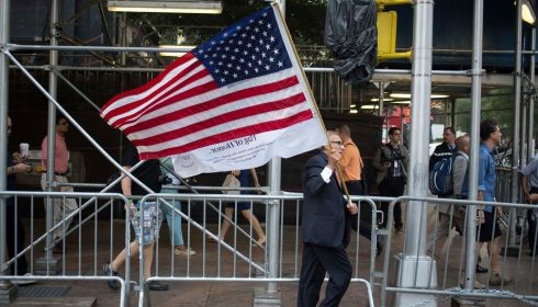 A man walks with a US flag outside the site of the World Trade Center in New York today. Photograph: Reuters