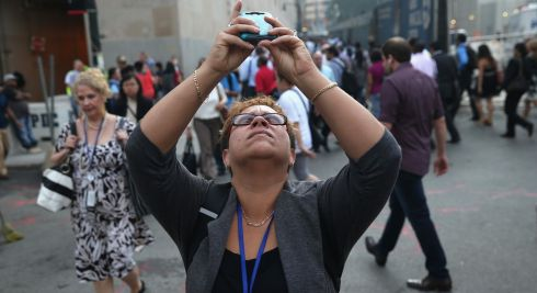 A woman photographs the World Trade Center as church bells toll for the victims of the terrorist attacks. Photograph: John Moore/Getty Images