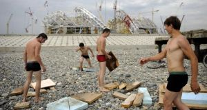 Collision course?: workers take a break as building continues on Fisht Olympic stadium, in Sochi. Photograph: Mikhail Mordasov/AFP/Getty