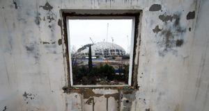 Collision course: Fisht Olympic stadium under construction in Sochi, seen through the window of a derelict house. Photograph: Leon Neal/AFP/Getty