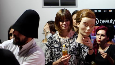 That is an amazing hat, at left...how it looks as the hairstylists ply their trade backstage at the Bora Aksu Spring/Summer 2014 collection. Photograph: Suzanne Plunkett/Reuters