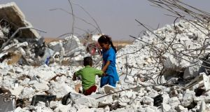 A girl helps her brother make his way through the rubble of a damaged house  in the eastern Hama countryside. Photograph: Reuters