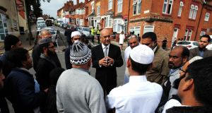 British  MP Keith Vaz (centre) meets residents yesterday near  the scene of a house fire (in background) at Wood Hill, in the Spinney Hills area of Leicester, which claimed the lives of Shehnila Taufiq and her three children. Photograph: Rui Vieira/PA Wire