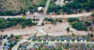 An aerial view shows flood waters and a washed-out road adjacent a suburban neighborhood in Lyons, Colorado, yesterday.  Photograph: John Wark/Reuters