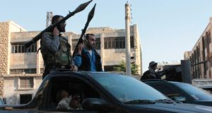 Free Syrian Army fighters hold their weapons while riding on a vehicle before heading to fight in Aleppo's district of Salaheddine.  Photograph: Reuters/Aref Hretani