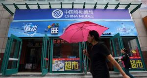 A pedestrian holding an umbrella walks past a China Mobile store in Dalian, China. Photograph: Tomohiro Ohsumi/Bloomberg