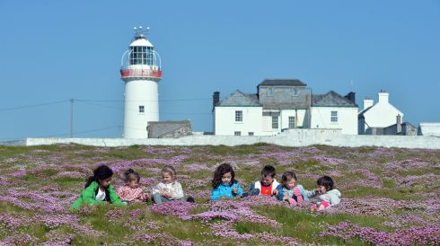 Children playing in front of Loop Head lighthouse during the summer. Loop Head has won The Irish Times Best Place to Holiday in Ireland Award. Photograph: Alan Betson/The Irish Times