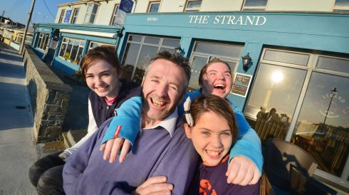 Johnny Redmond, fourth-generation owner of the Strand Bar and accomodation, with his daughters Laura, Sarah and Jayne on the seafront at Kilkee. Photograph: Alan Betson/The Irish Times