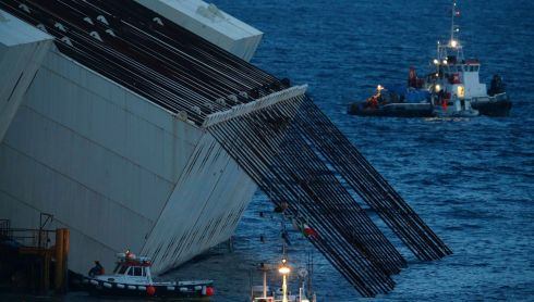 A series of immense cables are attached to tanks mounted on the side of the Costa Concordia. The tanks will be used for ballast while the cables will help to pull the vessel upright in the parbuckling operation.  Photograph: Tony Gentile/Reuters