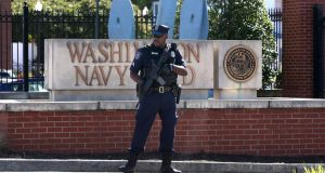 An armed guard stands outside the Washington DC naval facility following Monday's shootings. Aaron Alexis's job loss is being considered as a triggering factor for his killings. Photograph: Mark Wilson/Getty Images