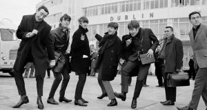 Twist and shout: The Beatles after arriving at Dublin Airport in November 1963, with Paul Russell (left) and  Frank Hall of RTÉ. Photograph: Lensmen Photographic Agency/irishphotoarchive.ie