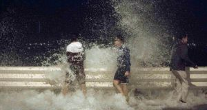 People react as waves splash on to the road during Typhoon Usagi in Hong Kong. The powerful typhoon killed at least 25 people after making landfall in Hong Kong and south China's Guangdong province at the weekend. Photograph:  Tyrone Siu/Reuters