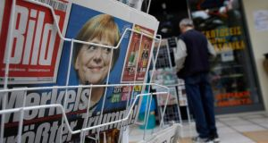 A photograph of German chancellor Angela Merkel looks out from the front page of Bild on a newspaper stand following her election victory, in Corinth, Greece, yesterday.  Photograph: Kostas Tsironis/Bloomberg