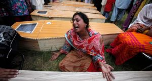 A Christian woman mourns next to the coffin of her brother, who was killed in the  suicide attack. Photograph: Reuters.