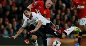 Manchester United's Phil Jones  challenges Liverpool's Luis Suarez during their English League cup game  at Old Trafford. Photograph: Phil Noble/Reuters