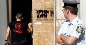 A Greek police officer watches as a member of the Golden Dawn far-right party enters the party's headquarters in Athens. Photogrpah: John Kolesidis/Reuters