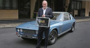 Author William Boyd holding his new James Bond novel, Solo, in front of a Jensen FF outside the Dorchester hotel in London. Photograph: Philip Toscano/PA Wire