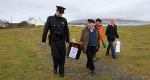 'Inishfree does officially have a population – a very small one – but only for a few weeks a year, in summer homes.' Above, Garda  Ronan McNamara  carries the ballot box away with presiding electoral officer Hugh O'Donnell  and two local residents from a house that was used as a polling station, on Inishfree off the Donegal coast in  2011. Photograph:   Peter Muhly/AFP/Getty Images