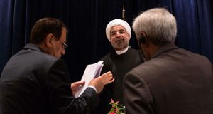 Iran's president Hassan Rouhani (centre) is approached by staff members after a news conference in New York today. Mr Rouhani said  he wanted talks with major powers on Iran's nuclear program to yield results in a short period of time and that the improved mood in US-Iranian relations could lead to better ties. Photograph: Adrees Latif/Reuters