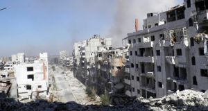 Smoke rises from buildings after what activists say was an air strike by forces loyal to Syrian president Bashar Al-Assad in Homs on Thursday. Photograph:  Reuters/Thaer Al Khalidiya