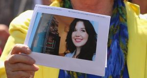 A woman holds a photograph of Jill Meagher aloft as people walk along Sydney Road in Brunswick in a peace march to mark the first anniversary of her murder in Melbourne, Australia. Photograph:  Scott Barbour/Getty Images