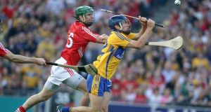 Clare's Shane O'Donnell scores his third goal despite the attention of Cork's Brian Murphy. Photo:Morgan Treacy/Inpho