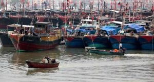 Fishermen drive a boat next to fishing ships docked at a port to shelter from Typhoon Wutip in Sanya, in China's Hainan province. Photograph: Reuters