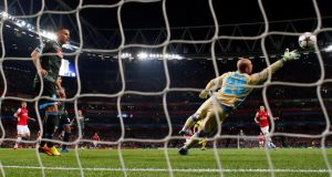 Arsenal's Mesut Ozil scores against Napoli during their Champions League  match at the Emirates stadium in London last night. Photograph: Eddie Keogh/Reuters