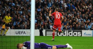Manchester City goalkeeper Joe Hart lies dejected as Bayern Munich's Arjen Robben celebrates scoring his side's third goal of the game during the UEFA Champions League match at the Etihad Stadium in Manchester. Photograph:  Martin Rickett/PA Wire