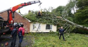 A  fallen tree is removed from a house yesterday in Clonfert, Co Galway earlier.  Photograph: Joe O'Shaughnessy