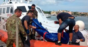 The body of a drowned migrant is unloaded from a coast guard boat in the port of Lampedusa, Sicily, yesterday.