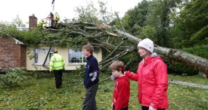 Brenda Coughlan with her sons Jack and Brendan (left) at their home as the fallen tree is removed yesterday at Clonfert, Co Galway. Photograph: Joe O'Shaughnessy.