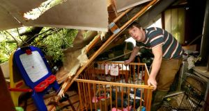 Noel Kelly with the cot in which his son adam was in when his mobile home was hit by fallen trees during the freak weather at Killoran, Clonfert, Co Galway. Photograph: Joe O'Shaughnessy.