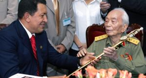 Venezuela's then president Hugo Chavez (left) offers a sword, similar to the one used by Venezuela's hero Simon Bolivar, to Vietnam's General Vo Nguyen Giap at his home in Hanoi in 2006. Photograph: Hoang Dinh Nam/Pool/Files